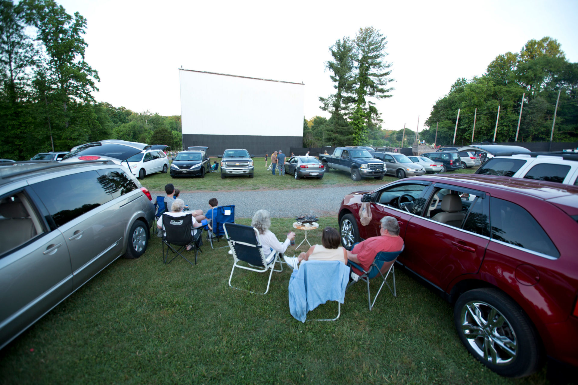 A group of people sitting in chairs by their cars waiting on the movie to start.